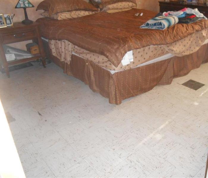 Master bedroom with bed (brown bedding) that shows the tile floor repaired
