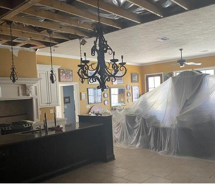 Ceiling removed to dry structure; plastic sheeting on dining room table