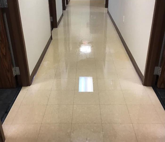 Office hallway with water on a tile floor