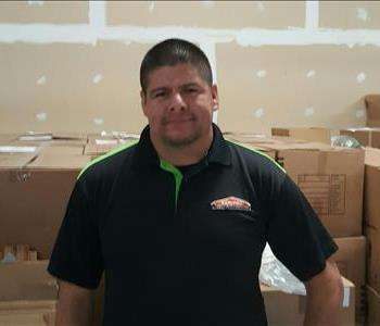 Male worker in black shirt with SERVPRO orange house logo on the pocket