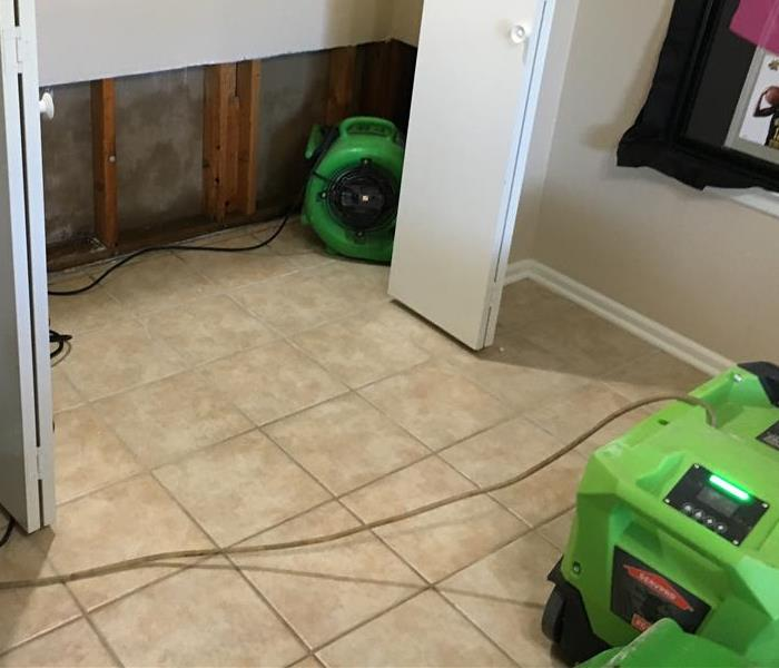 One air mover, green, in a closet with walls flood cut, and a green dehumidifier on tile flooring