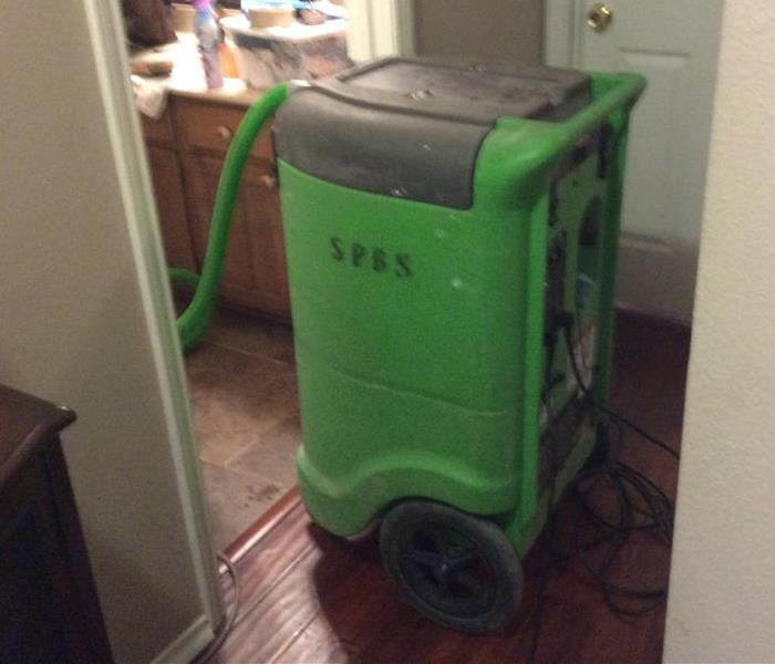 Green extractor in a hallway with hose in the bathroom