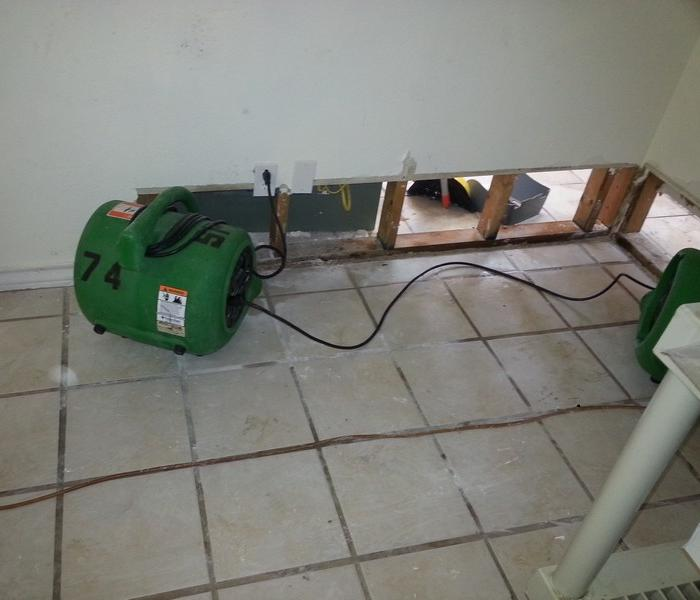Two green air movers drying a wall cavity on tile flooring.  The wall has a flood cut in it.