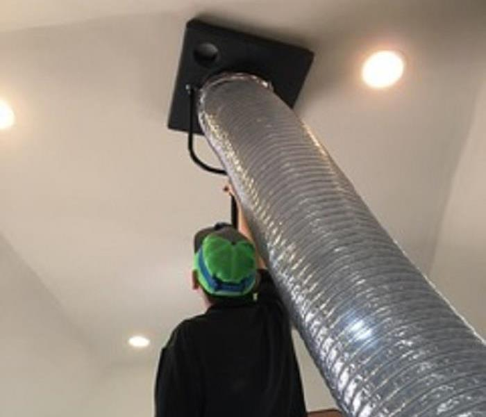 Men in green baseball hat, next to silver duct work