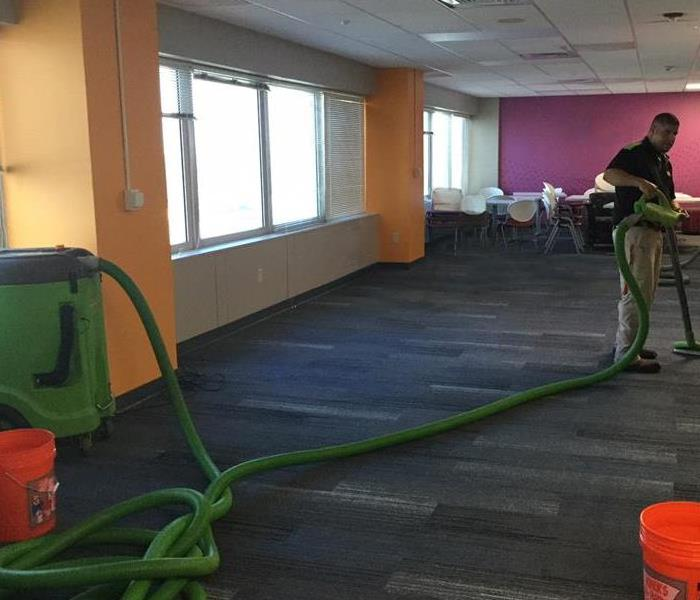 Man using green extractor to extract water from a commercial office's carpet
