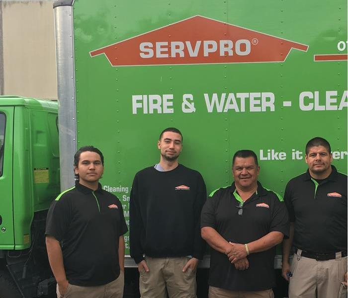 Four workmen in black shirts in front of a SERVPRO box truck