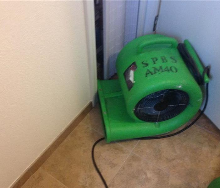 Green Air mover blowing air toward a closet door