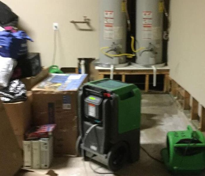 Garage with two pieces of green drying equipment and flood cuts on the walls