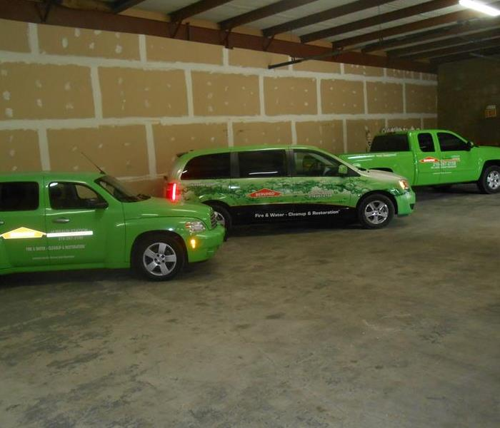 Three green vehicles in a warehouse