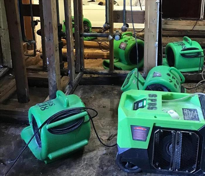 Professional SERVPRO green air movers and dehumidifiers are placed in dining room with no floor and torn out drywall