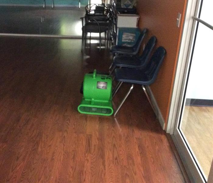 Green air mover next to blue chairs in an office