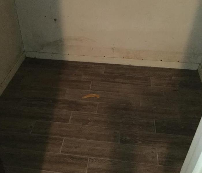Closet with brown hardwood dirty from water and wall dirty from flood water