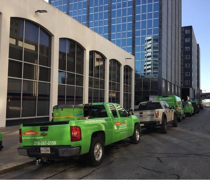 The SERVPRO Green Fleet Parked on the street in front of tall buildings.