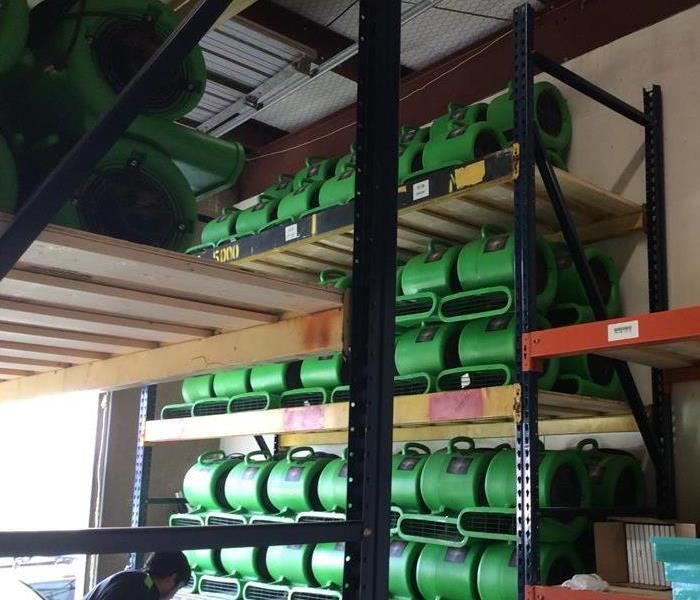 Green air movers stacked on shelves