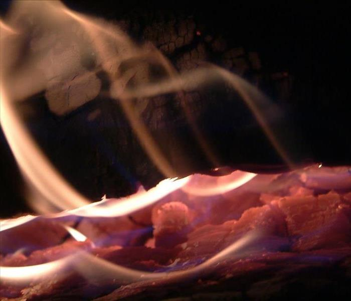 Coals on fire in a fireplace with smoke