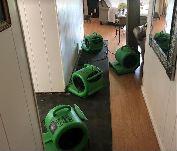 SERVPRO drying equipment being used in water damaged hallway
