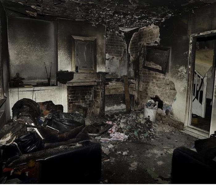 Living room with soot covered walls and several sections of drywall burned away